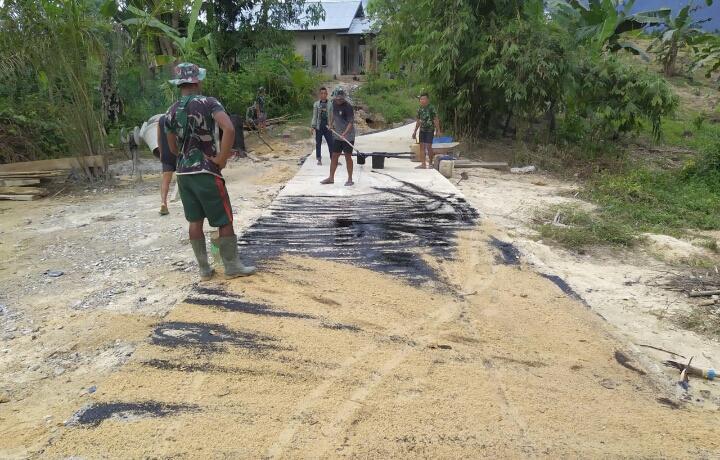 Satgas TMMD Ke 110 Menyiramkan Aspal Panas Ke Semenisasi Jalan Guna Lebih Tahan Lama